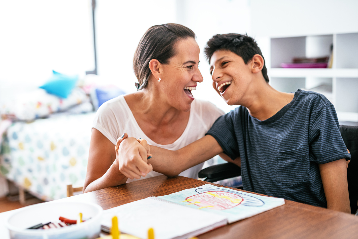 Disabled Latino teenager with mother laughing.